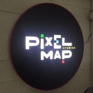 Logo circular de acero lacado con textos calados, metacrilato rotulado en vinilo de corte y luz LED